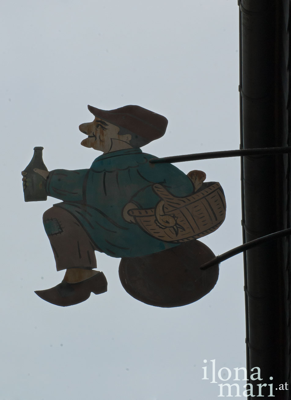 Ein Cidretrinker an der Fassade eines historischen Gebäudes in der Altstadt von Honfleur