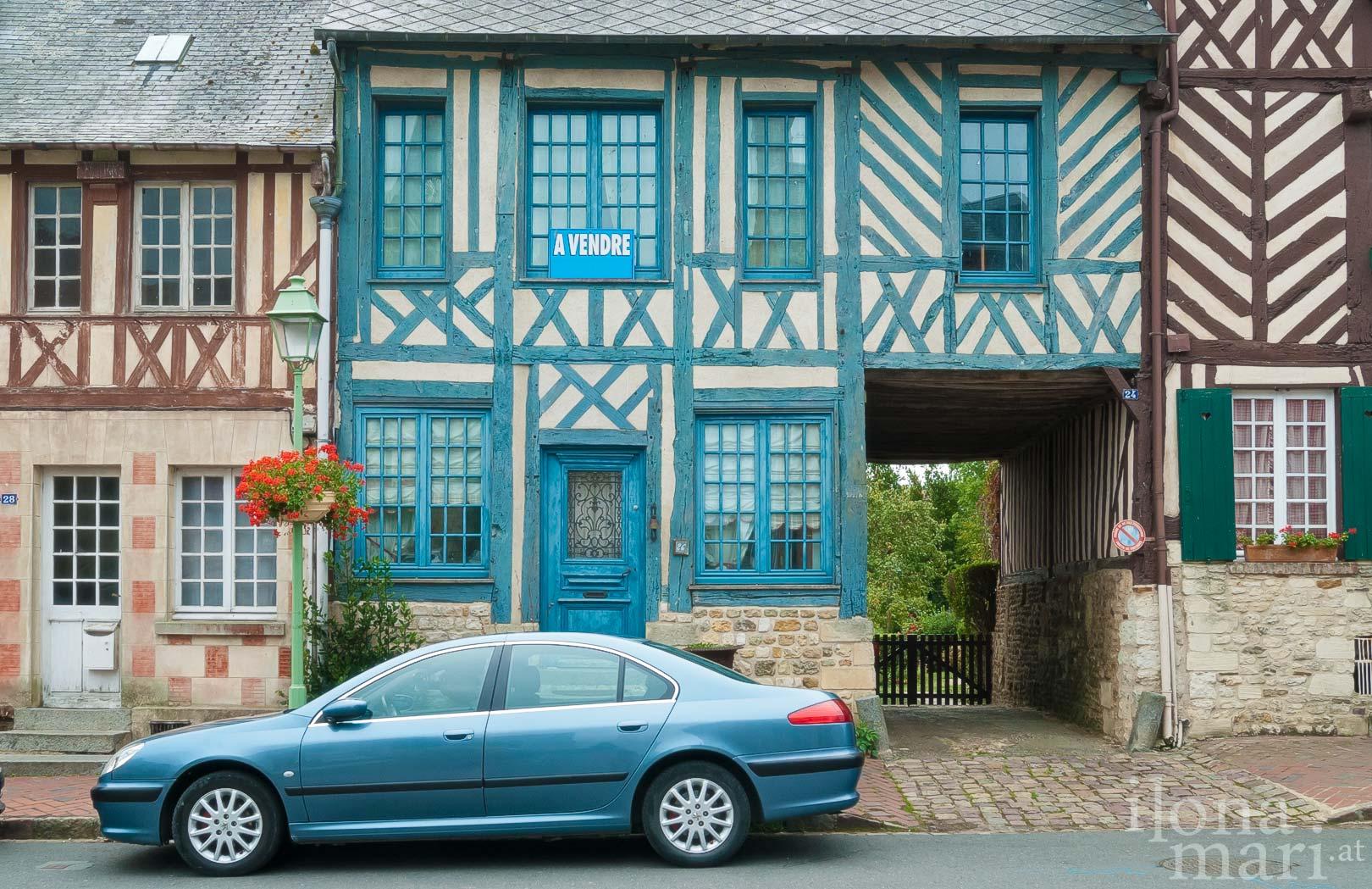Ein blaues Auto parkt vor einem blauen Fachwerkhaus in Beaumont-en-Auge (Normandie)