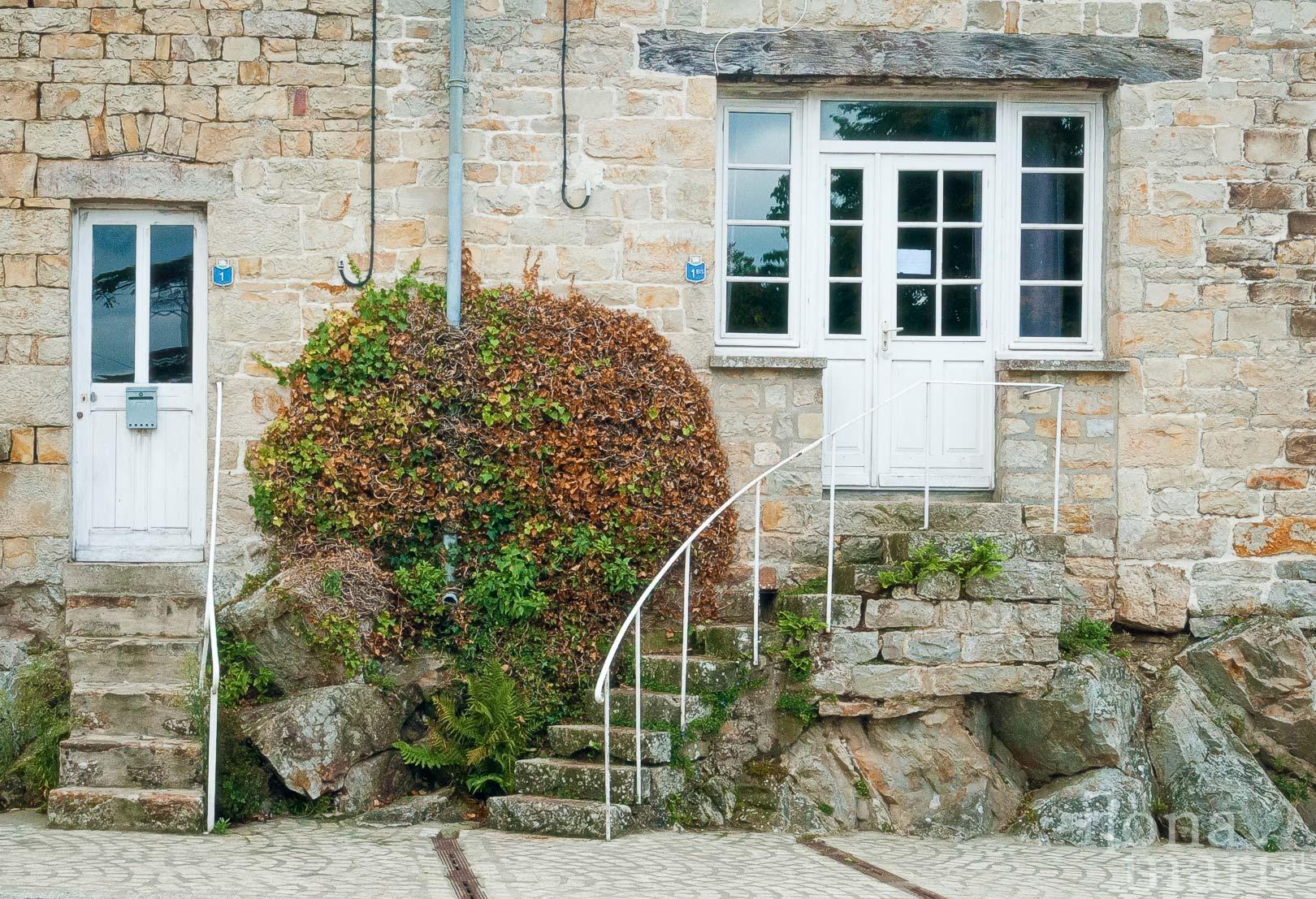 Steile Steintreppen führen zu den Eingängen der historischen Häuser von Domfront (Normandie)