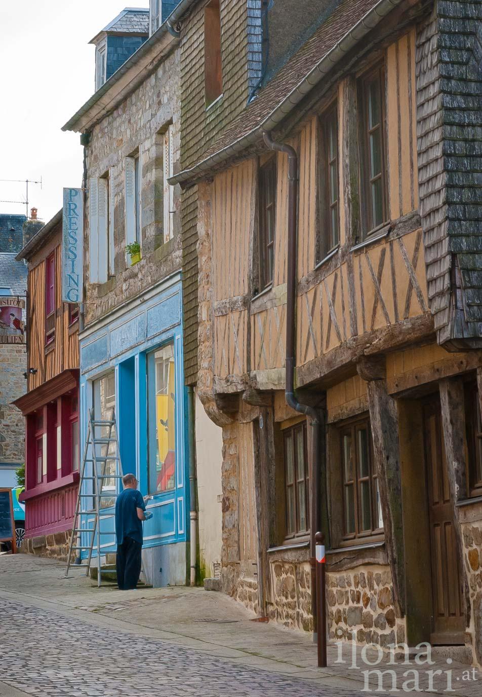 Streichen einer Ladenfassade in Domfront (Normandie)